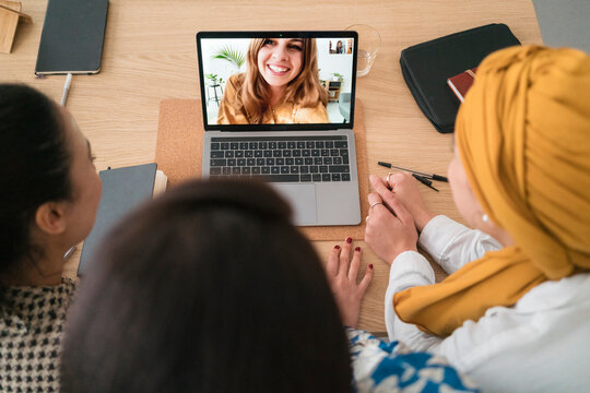 Diverse women having video call with colleague on laptop in office