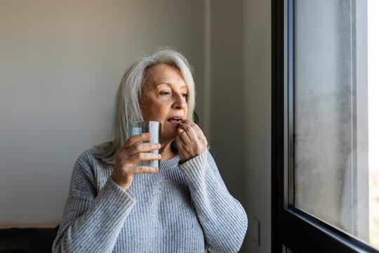 Mature woman taking vitamins pills
