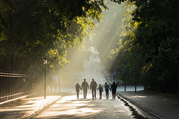 People walking the street lit by the sun after the rain