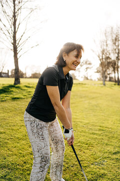 woman laughing while playing golf