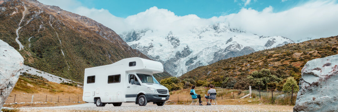Motorhome camper van RV road trip on New Zealand. Couple on travel vacation adventure. Tourists looking at view of Aoraki Mount Cook National park and mountains next to rental car. Panoramic banner