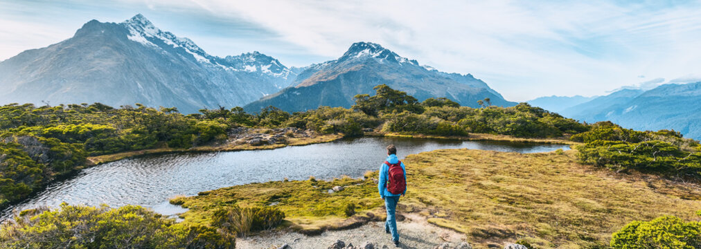 New Zealand Hiking. Young hiking man walking on trail at Routeburn Track during sunny day. Hiker tramping Key Summit Track in Fiordland National Park in New Zealand. Panoramic banner