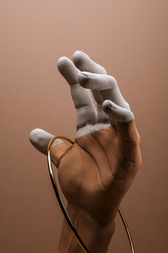 Painted white hand catching a gold hoop