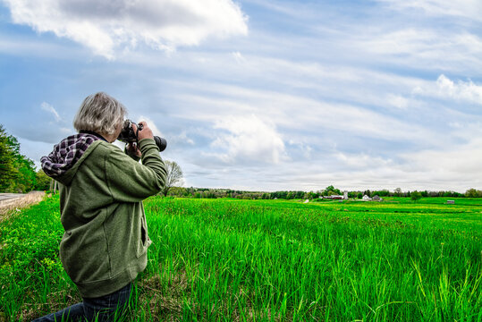 Elderly woman photographer,  taking  landscape photographs. Big blue sky puffy clouds. Room for copy text.