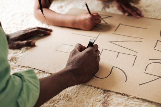 Close up of a girl and her father's hands preparing a banner for Black lives matter protests