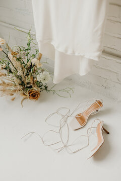 Wedding dress, flower arrangement and high heel open toe shoes on white floor