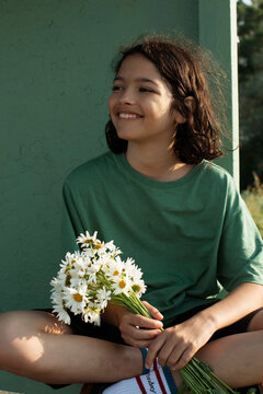 Cute  girl with a daisies on a bus stop