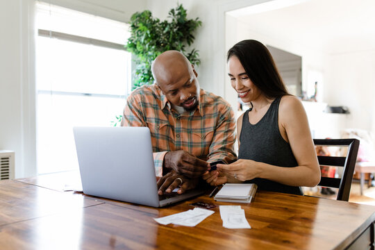 Young Couple Looks at Credit Card and Receipts