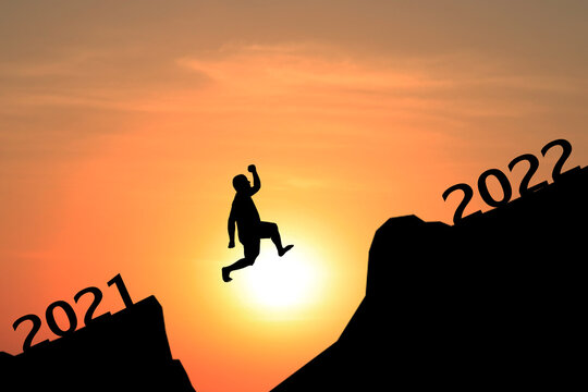 Silhouette of young man jumping between 2021 and 2022 years with beautiful sunset.