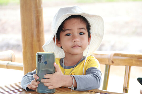 leisure, children, technology and people concept - smiling boy with smartphone and headphones having video call at home. child with mobil