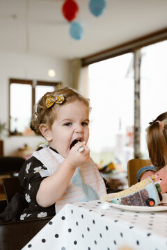 Toddler girl eating cake on a birthday party indoors