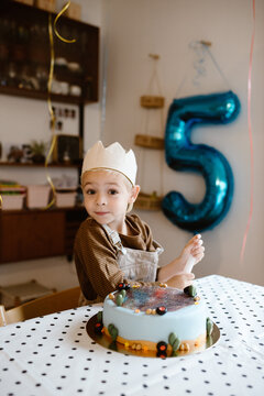 Birthday boy wearing a crown at home with cake and balloon