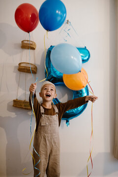 Toddler birthday boy with helium balloons indoors