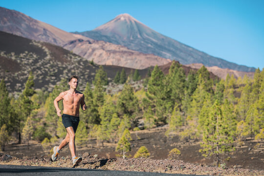 Running man athlete shirtless sprinting on road against nature volcanic mountain forest background landscape. Summer outdoor training active lifestyle.