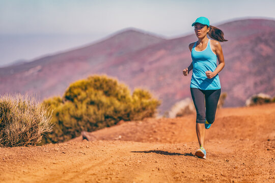 Asian athlete woman running outdoor on mountain trail. Fitness sports girl wearing cap for sun protection. People training in desert landscape Trail runner summer active lifestyle.