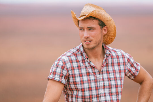 Cowboy man wearing western straw hat in country farm background. American Male model portrait in american countryside landscape nature on ranch or farm, Utah, USA.