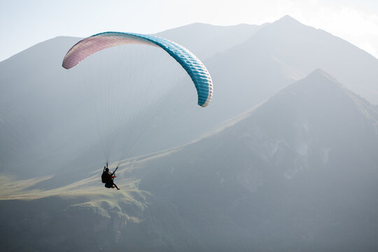 Paraglider flying over green ridge of mountains