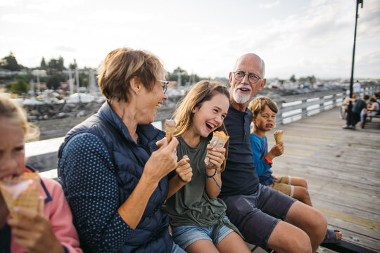 Grandparents and grandkids laugh and sit on a bench on a dock wh