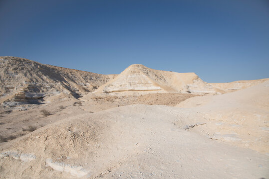 Beautiful lunar landscape. Wight and smooth hills in various shapes in a desert landscape. The whitish, rounded, winding, and smooth chalk rocks. Israel. High quality photo