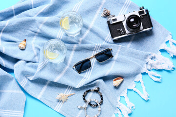 Fototapeta Stylish sunglasses with photo camera, glasses of water and scarf on color background obraz