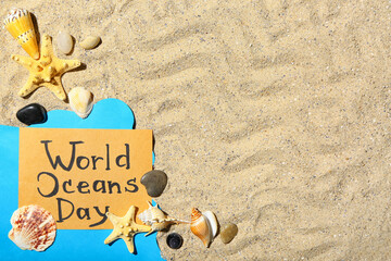 Fototapeta Paper sheet with text WORLD OCEAN DAY and sea shells on sand obraz