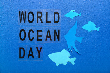 Fototapeta Text WORLD OCEAN DAY and paper fishes on color background obraz