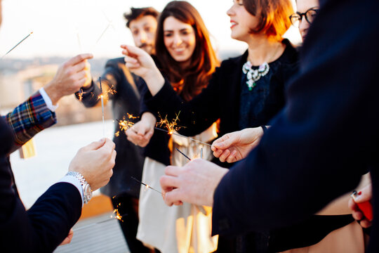 Crop happy partners with sparklers during party in sunlight outdoors