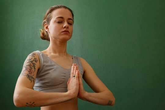 Focused woman meditating with prayer hands