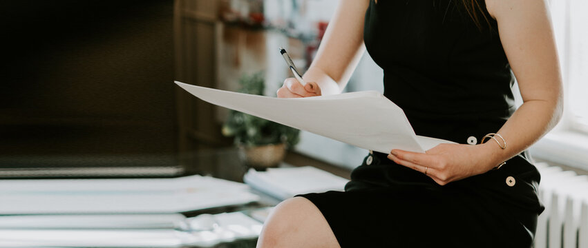 Businesswoman making notes looking at a cellphone at office
