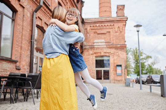 Candid portrait of happy mother and daughter with down syndrome having fun together outdoors in city, copy space