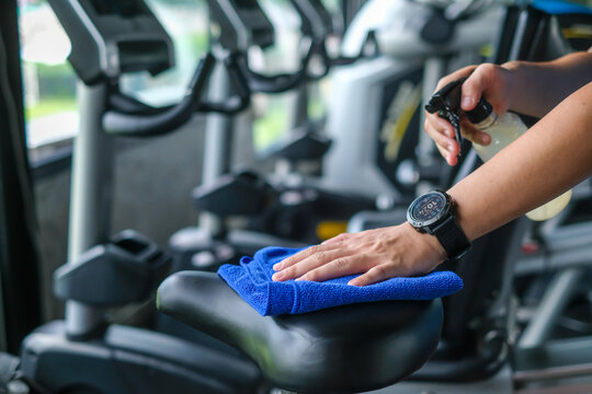 partial view of man cleaning sports equipment in gym on blurred foreground