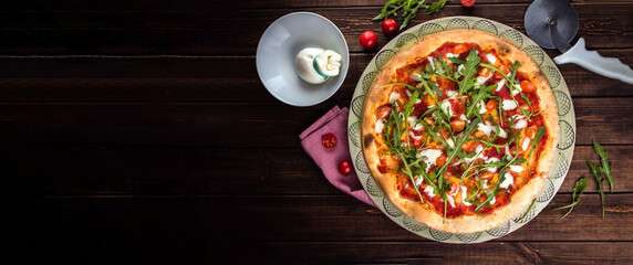 Top view banner with Pizza Margherita. Buffalo mozzarella, tomatoes and fresh basil. Pizza cutter and pink tablecloth lies on the wooden background. Vertical flat lay. Traditional italian fast food