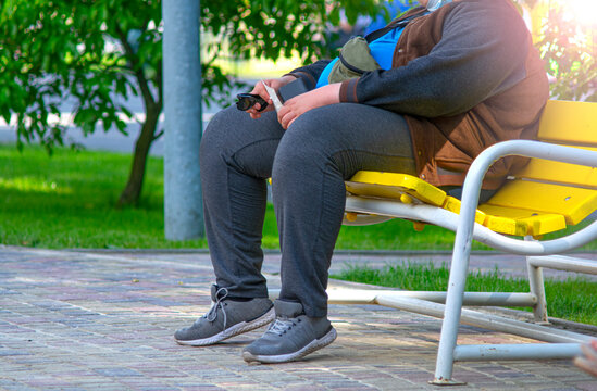 Overweight man resting on a bench in the park