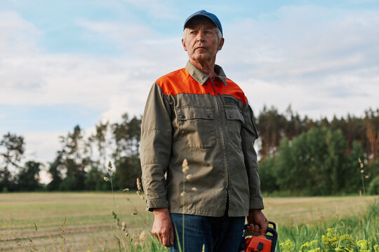 Portrait of mature man wearing jacket and cap posing outdoor in meadow with chainsaw in hands, looking in distance with pensive expression, looks around before working.