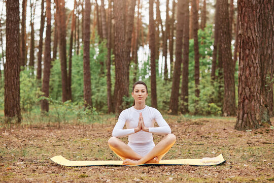 Young attractive female wears white sportsrwear sitting on karemat in lotus pose with pressed palms, trains in open air, meditating and doing yoga in forest, lookigng camera with serious expression.