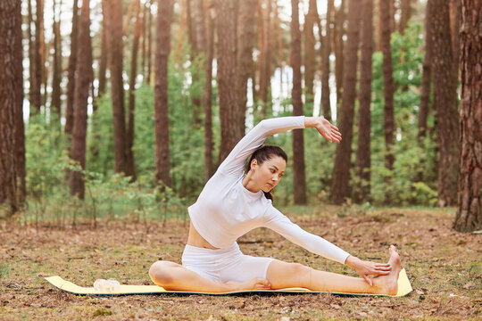 Outdoor portrait of dark haired woman with perfect body in white sportrswear stretching while sitting on karemat in forest, working out in park, doing yoga exercises.