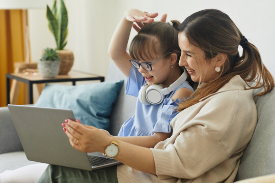 Portrait of cute girl with disability speaking to camera while using video chat with mom, copy space