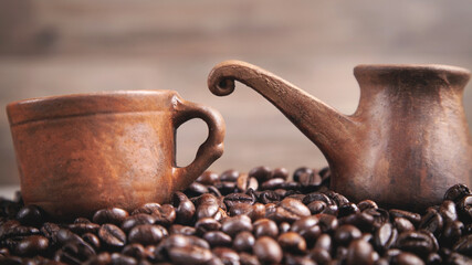 Clay coffee cup and pot on coffee beans.