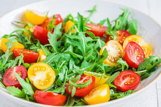 Arugula and tomatoes salad. Healthy vegan food concept.