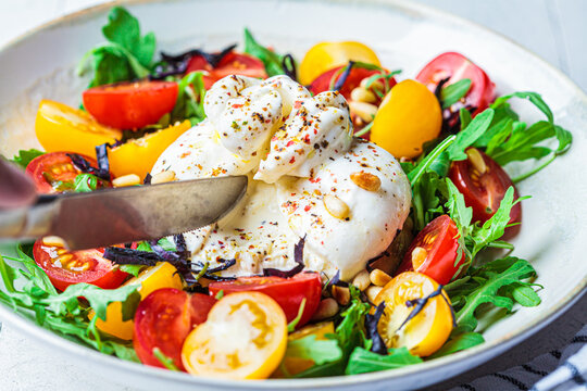 Close-up of burrata cheese salad with arugula, nuts and tomatoes.