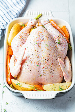 Uncooked whole chicken stuffed with thyme and lemon in dish for roast. Cooking meat concept.