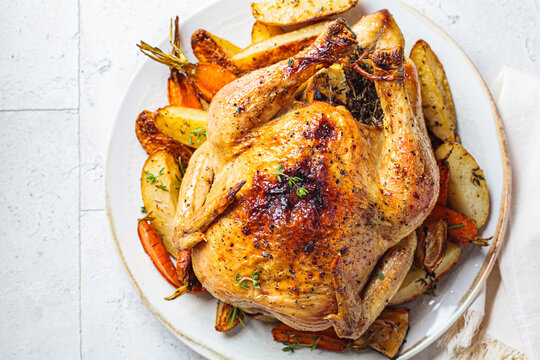 Baked whole chicken stuffed with thyme and lemon with vegetables.
