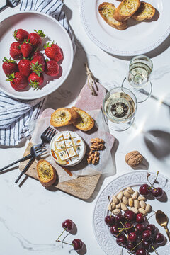 Baked Camembert or Brie with thyme and maple syrup. Flat lay of cheese, fruits, bread and nut to white wine.