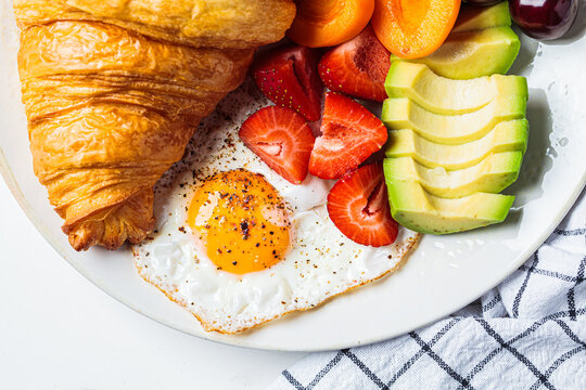 Breakfast plate with croissant, avocado, fried egg, salad and fruit.