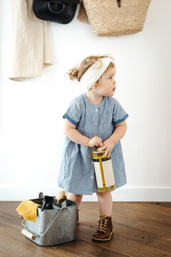 Toddler girl walking in the kitchen with tin bucket full of cleaning products