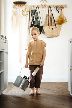 Toddler boy walking in the kitchen with tin bucket full of cleaning products