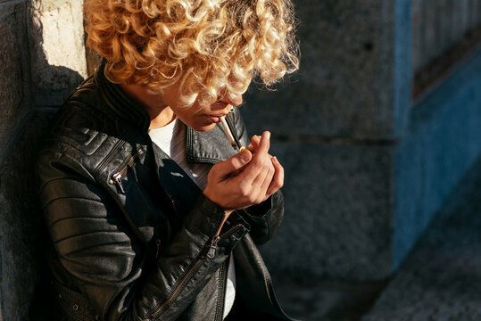 Adult woman smoking in street on sunny day