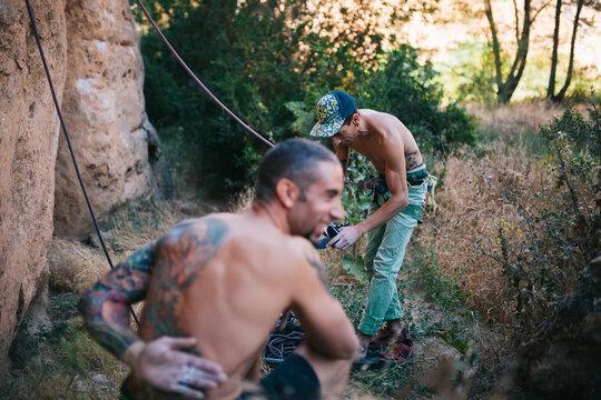 Cheerful tattooed mountaineers preparing for climbing rock