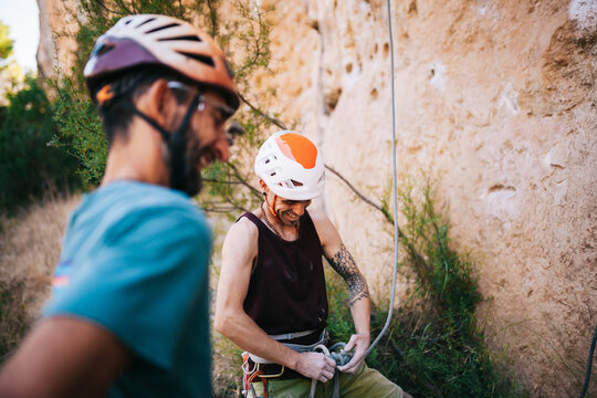 Cheerful mountaineers getting ready with climbing equipment