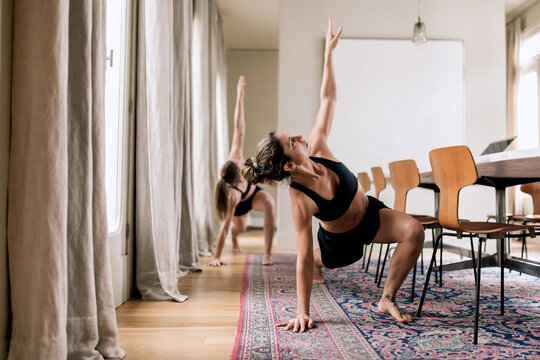 Trainer showing yoga exercise to woman